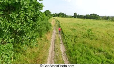 Running man on rural road outside in green field. Male runner jogging during outdoors training.