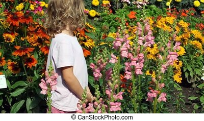 girl goes among set of flowers in garden examines and smells...
