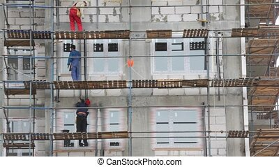 builders works on falsework in building area - three...