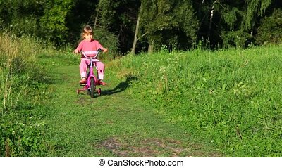 girl rides bicycle to camera in park - little girl rides...
