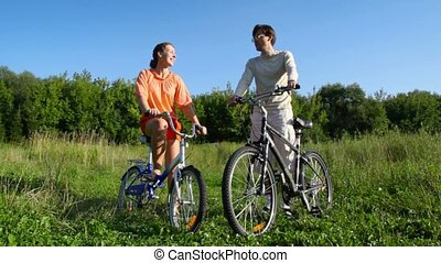couple on bicycles talks in field - happy couple on bicycles...