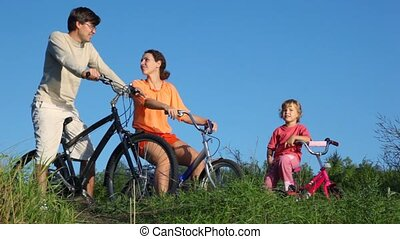 family with bicycles talks in summer park - happy family of...