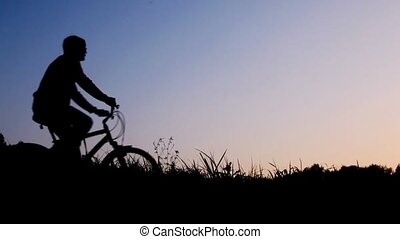 silhouette of man riding bicycle stops against sky -...