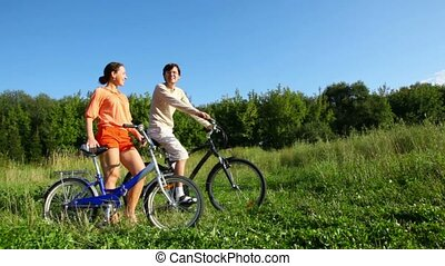man and woman with bicycles talks in field - man and woman...