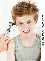 Young boy having ear examination - Portrait of smiling young...
