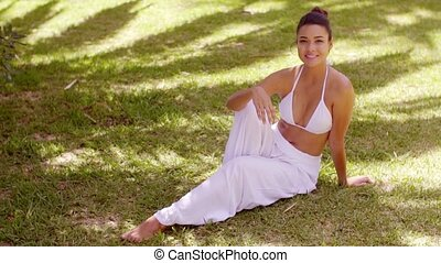 Smiling friendly young woman relaxing in a garden - Smiling...