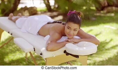 Happy young woman having a hot stone massage looking up at...