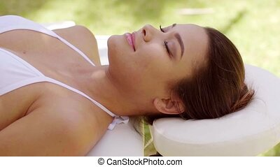 Single woman laying down in outdoor beauty spa - Single...