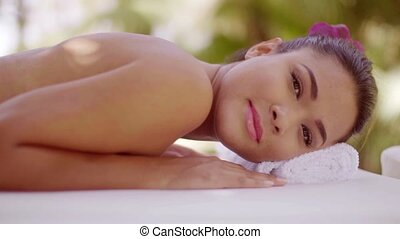 Gorgeous natural young woman relaxing at a spa with her head...