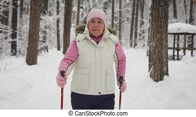 An elderly woman in a beautiful sports wear is engaged in Nordic walking on a snowy path in winter forest. Modern pensioner actively pursuing their leisure time outdoors.