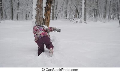 Little girl playing with snow, clearing himself a path in...