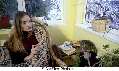 attractive young woman sits in the chair and wrap into the...