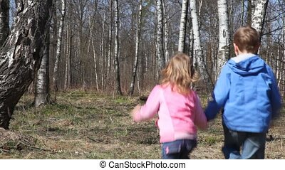 boy with sister runs to spring forest - boy with little...