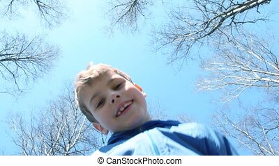 boy against spring sky - smiling boy looks top-down at...