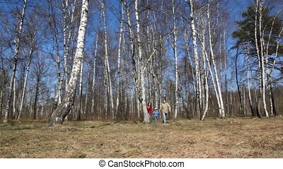 family with son comes to camera in forest - family of three...