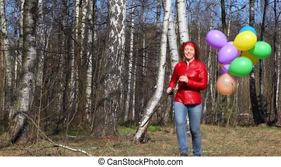 woman with balloons runs in spring grove - happy young woman...