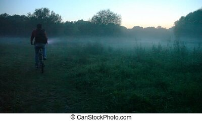 man with electric torch rides bicycle in forest - man with...