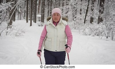The elderly woman spends leisure-time in the wood. Winter...