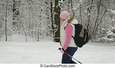 The woman in the wood in the winter. The pensioner by means of special sticks is engaged with the wood in the Scandinavian walking. The elderly woman for a healthy lifestyle