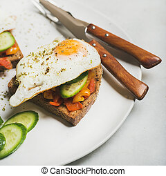 Breakfast toast with fried eggs, vegetables. square crop -...