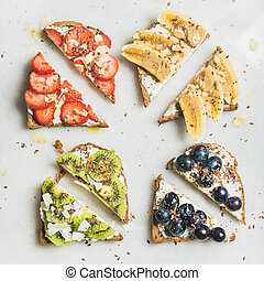 Healthy toasts with cream-cheese, fruit, nuts and seeds,...