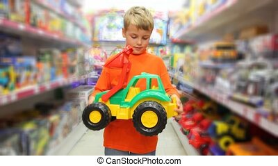boy examines toy excavator in store