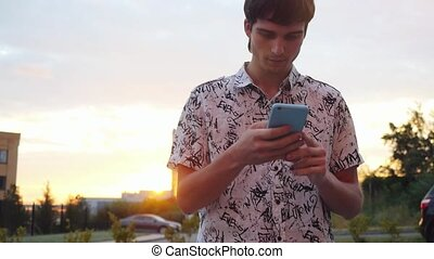Young handsome businessman using smartphone outdoors at...