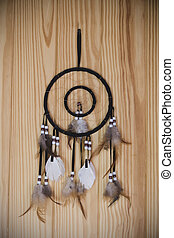 Dream catcher with feathers on wall wood background
