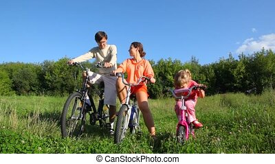 family with bicycles in field against forest - family of...
