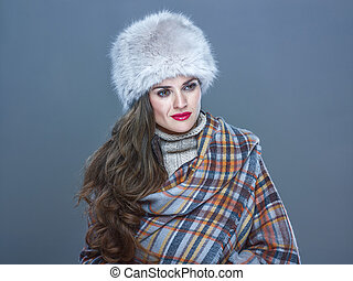 Portrait of pensive trendy woman in fur hat isolated on cold...