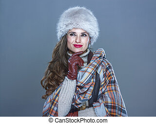 pensive modern woman isolated on cold blue looking on copy...