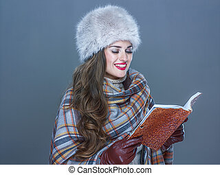 happy modern woman in fur hat isolated on cold blue reading...