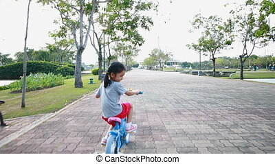 Asian little girl riding a bicycle in public park with...