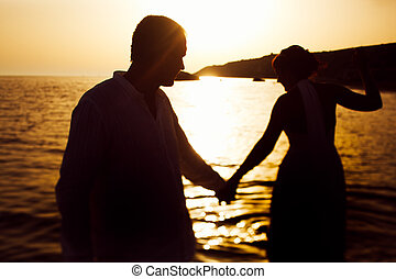 Silhouettes of a couple walking in the water to the sunset