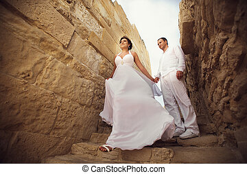 Bride walks down the sand footsteps holding groom's hand