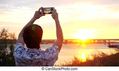 Young man taking photo of amazing sunset using smartphone on the beach on the blurred bridge background. 3840x2160