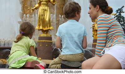 Mother, son and daughter sit near Fountain Friendship of...