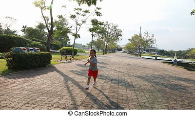 Asian little girl running in public park with camera follower