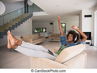 African american woman at home in chair with tablet and head...