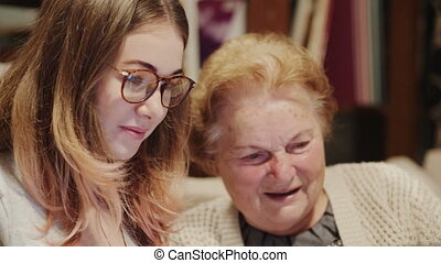 Young woman helping an old senior woman with laptop computer