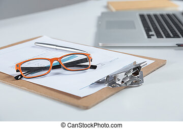 Closeup of white desktop with laptop, glasses, coffee cup,...