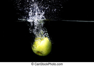 Green apple falling in water with splash on black background.