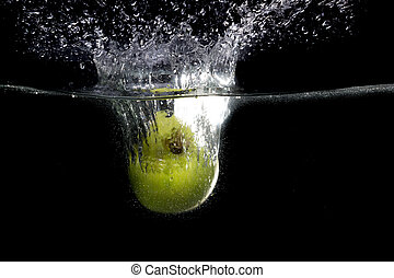 Green apple falling in water with splash on black background