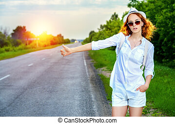 girl catching a car - Hitchhiking girl. Attractive young...