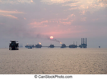 Sunset over oil complex - Oil complex and offshore...