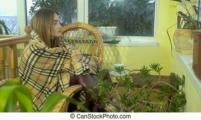 beautiful young girl sitting in a Wicker Chair and is...
