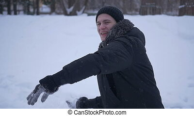Man smiling throwing snow directly into the camera - Boy...