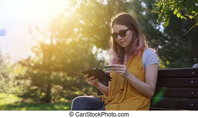 Shopper girl buying online with a laptop and credit card lying in a park in summer