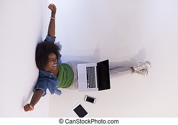 african american woman sitting on floor with laptop top view