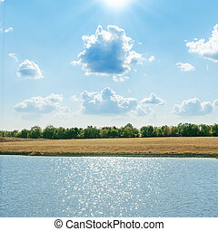 dramatic clouds in blue sky with sun over pond